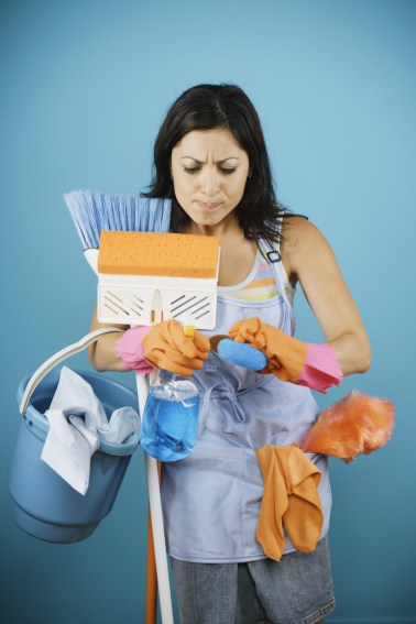 Young woman loaded with cleaning supplies